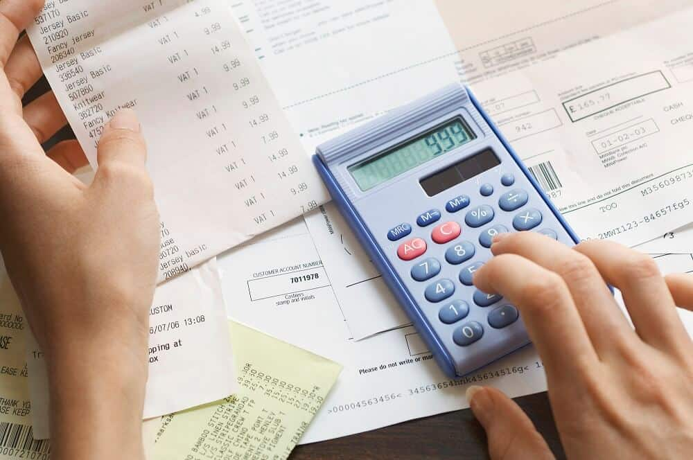 Woman calculating the cost of a merchant cash advance with a calculator